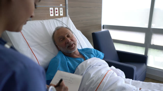 friendly nurse checking on senior hospitalized patient taking notes on notepad both smiling - south america stock videos and b-roll footage