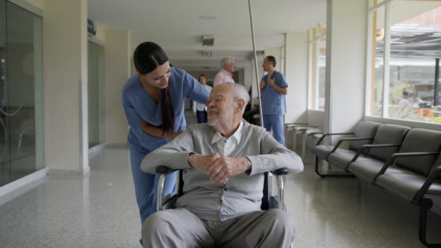 friendly nurse talking to senior patient while pushing him on wheelchair at the hospital's corridor - civilian stock videos & royalty-free footage