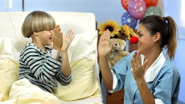 vídeos de stock, filmes e b-roll de hd dolly: enfermeira para o palhaço com nariz vermelho - enfermeira pediátrica