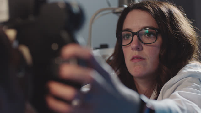 stockvideo's en b-roll-footage met cu ots. friendly optometrist lifts phoropter and chats with patient during eye exam. - 30 34 jaar
