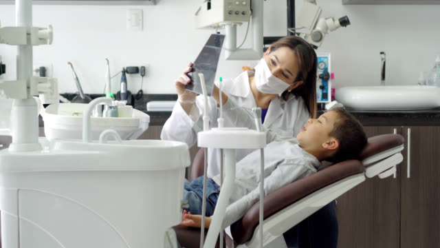 friendly pediatric dentist talking to her little patient and showing him an xray - dental hygiene stock videos & royalty-free footage