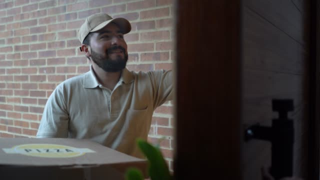 friendly pizza delivery guy handing order to unrecognisable customer at home - delivering stock videos & royalty-free footage