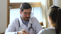 Friendly professional male doctor consulting woman patient at medical consultation