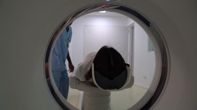 stockvideo's en b-roll-footage met vriendelijke radioloog het krijgen van een vrouwelijke patiënt klaar voor een hersenscan - operatiekleding
