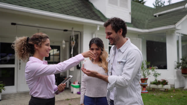 friendly realtor handing the keys to their new home to couple while they hug very excited - estate agent stock videos & royalty-free footage