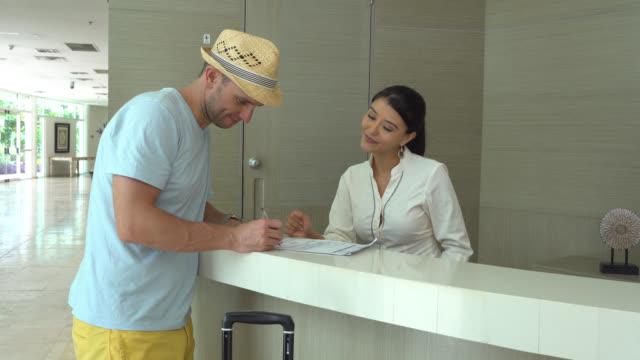 フレンドリーな receiptonist ご到着時にホテルのゲストにキーを手渡し - ゲスト点の映像素材/bロール