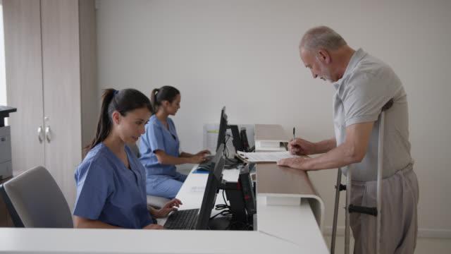 vídeos de stock, filmes e b-roll de recepcionista amigável ajudando homem com deficiência preencher um formulário no hospital antes de sua nomeação - secretária