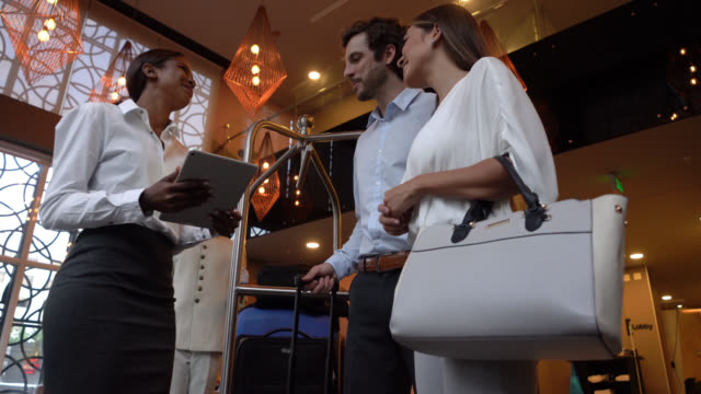 friendly receptionist helping guests fill in a survey on tablet and then they hand there luggage to bellhop - checkout stock videos and b-roll footage