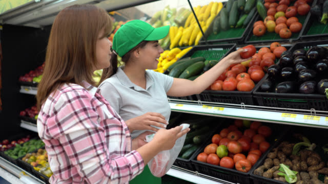 friendly sales clerk helping mature woman choose vegetables at the refrigerated section of a supermarket - assistant stock videos & royalty-free footage
