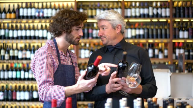 Friendly salesman asking questions about the differences of the wine to business owner of a winery both looking happy