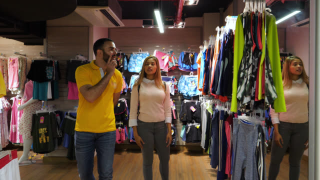 friendly salesman helping a beautiful young client choose options at a clothing store - clothing store stock videos and b-roll footage