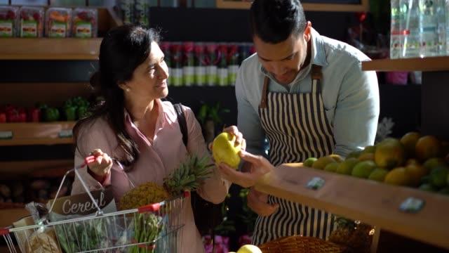 freundliche verkäufer hilft der kundin, die früchte zu wählen, während sie sie in ihrem warenkorb hinzugefügt - protective workwear stock-videos und b-roll-filmmaterial