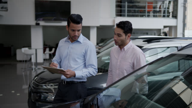 vídeos de stock, filmes e b-roll de vendedor amigável mostrando um carro para cliente masculino explicando as propriedades do carro enquanto segura uma prancheta - sale