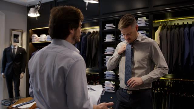 stockvideo's en b-roll-footage met vriendschappelijke verkoper die een knoop neer overhemd en een stropdas aan mannelijke klant bij een herenopslag voorstelt - kledingwinkel
