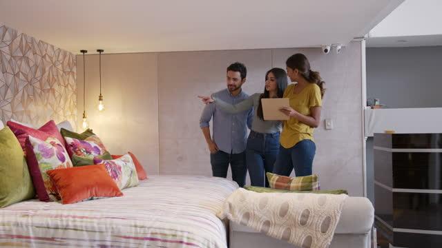 vidéos et rushes de vendeuse amicale aidant un jeune couple gai tandis qu'elle suggère différents tissus pour une chambre à coucher à un magasin textile - lit ameublement