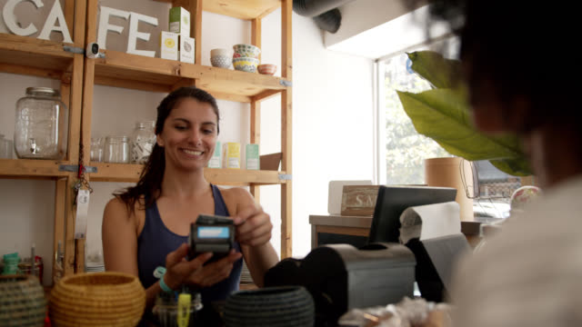 vídeos de stock, filmes e b-roll de vendedora amigável em um cliente charing da loja de café para um café quando pagar com um cartão de crédito - pequenas empresas