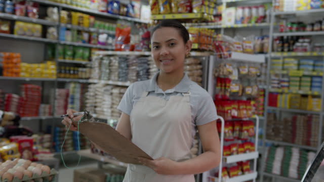 friendly saleswoman at a small market holding a clipboard doing inventory and then smiling at camera - market trader stock videos & royalty-free footage
