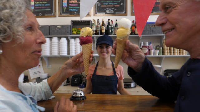 friendly saleswoman at the ice cream parlor handing ice creams to a senior couple toasting with them and looking very happy - serving scoop stock videos & royalty-free footage