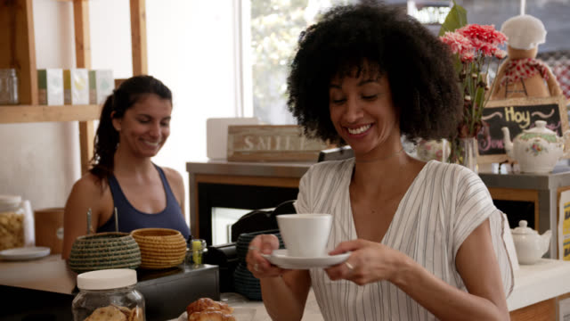 friendly saleswoman handing a coffee to black female customer very cheerfully - giving stock videos & royalty-free footage
