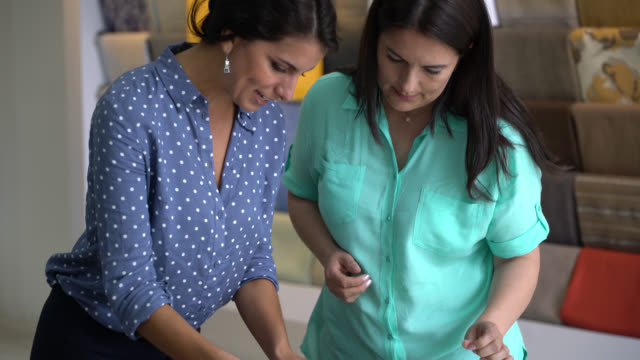 フレンドリーな店員がよほど繊維を組み合わせて顧客を支援 - 生地サンプル点の映像素材/bロール
