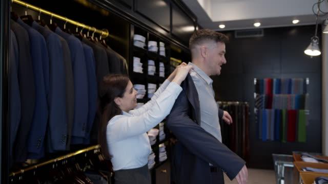 stockvideo's en b-roll-footage met vriendschappelijke verkoopster die een knappe zakenman helpt tryout een blazer bij een kledingopslag - kledingwinkel