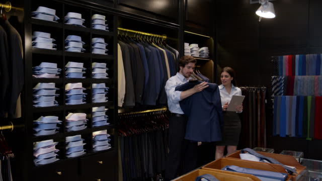 friendly saleswoman using a tablet to write take male customer's order while he looks at different formal jackets - tuxedo stock videos & royalty-free footage