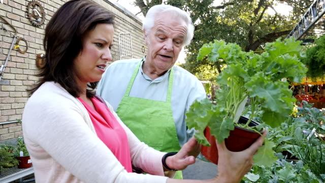 Friendly senior adult sales clerk explains kale selection to mid-adult female