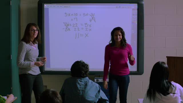 a friendly teacher encourages a student as she successfully completes an equation. - interactive whiteboard stock videos & royalty-free footage