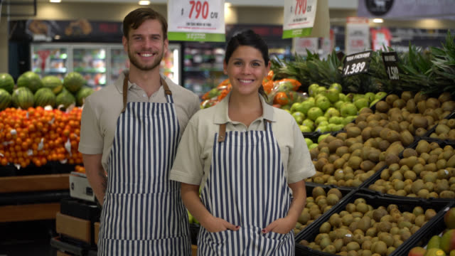 friendly team of sales people at the supermarket wearing aprons and facing camera smiling - shop assistant stock videos & royalty-free footage