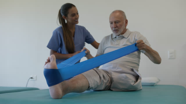 friendly therapist supporting senior amputee male patient working out with a stretch band during physical rehab - amputee stock videos & royalty-free footage
