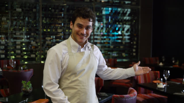 friendly waiter at a hotel restaurant welcoming with a hand gesture while looking at camera - hotel stock videos & royalty-free footage