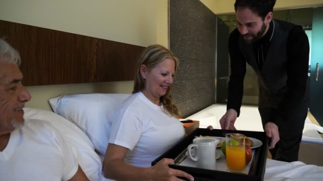 Friendly waiter bringing room service breakfast to a senior couple in bed at the hotel smiling
