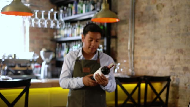 friendly waiter holding a bottle of wine while looking at it and then facing the camera smiling - bar drink establishment stock videos and b-roll footage