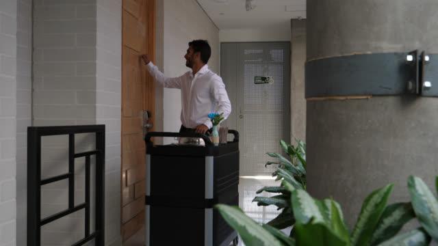 stockvideo's en b-roll-footage met vriendelijke ober kloppen op de deur te leveren van de roomservice - dienstverlener