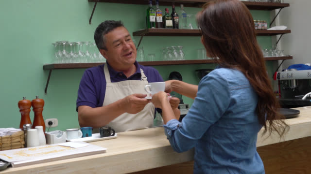 friendly waiter serving a coffee for a beautiful customer at a coffee shop behind the counter - giving stock videos & royalty-free footage