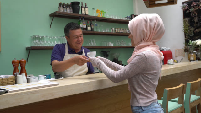 friendly waiter serving a coffee for a muslim customer at a coffee shop behind the counter - giving stock videos & royalty-free footage