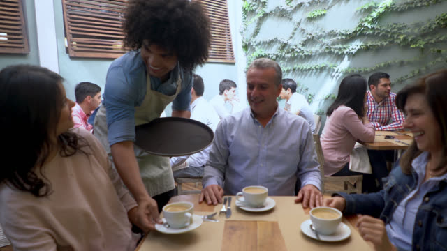 Friendly waiter serving coffee to a group of adults looking very happy