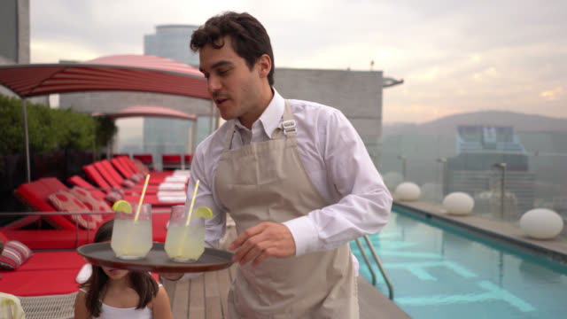 friendly waiter taking lemonade to happy family enjoying a beautiful day at the rooftop hotel pool - hotel stock videos & royalty-free footage
