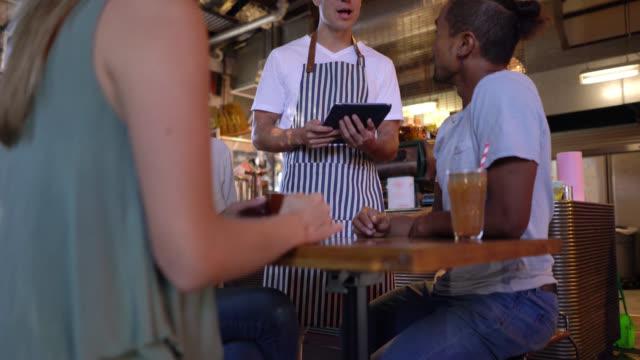 freundliche kellner, die aufnahme der bestellung auf tablet von einer gruppe junger freunde - café stock-videos und b-roll-filmmaterial