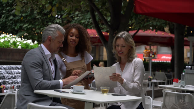 friendly waitress taking the order of a couple at a restaurant using a tablet while suggesting food - ordering stock videos & royalty-free footage