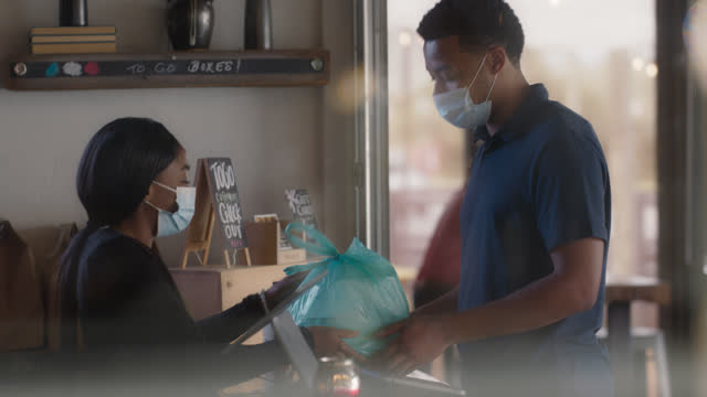 friendly waitress wearing a mask brings out a takeout order to a young man - restaurant stock videos & royalty-free footage