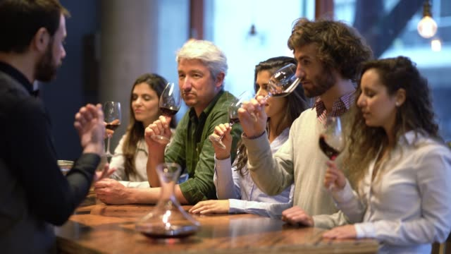 friendly wine steward telling his customers to smell the wine at a wine tasting all looking happy and curious - wine stock videos & royalty-free footage