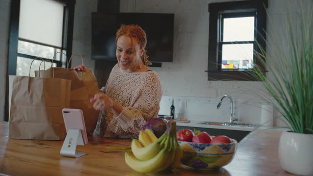 vídeos y material grabado en eventos de stock de friendly woman smiles and laughs as she unpacks her groceries while video chatting on her mobile phone - consumismo