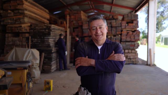 freundlicher holzfabrikleiter mit blick auf kamera lächelnd kreuzende arme - arme verschränkt stock-videos und b-roll-filmmaterial