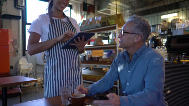 friendly young waitress taking an order on tablet from cheerful male client - waiter stock videos & royalty-free footage
