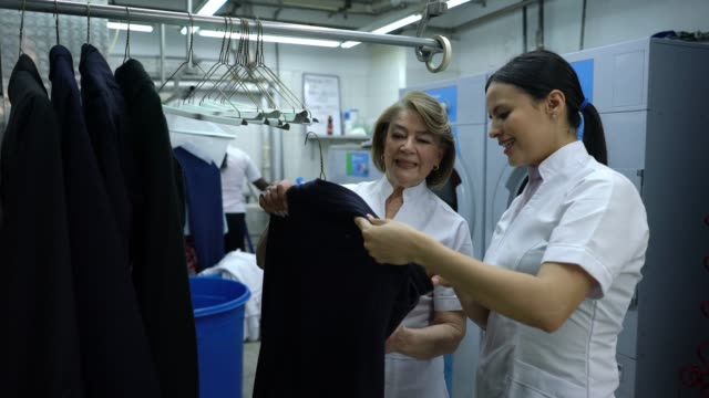 Friendly young woman training a mature woman at an industrial laundry explaining something about a garment on coat hanger