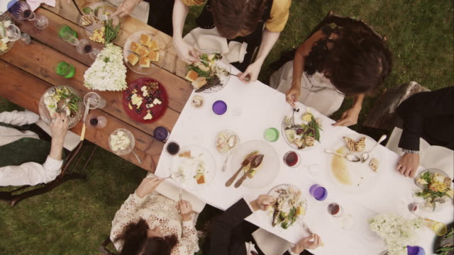 friends and family eating at an outdoor dinner party - speisen stock-videos und b-roll-filmmaterial