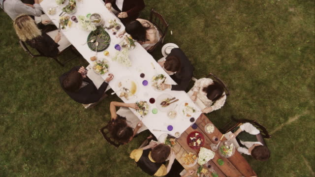 friends and family eating at an outdoor dinner party - zoom out stock videos & royalty-free footage