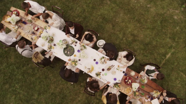 friends and family eating at an outdoor dinner party - im freien stock-videos und b-roll-filmmaterial