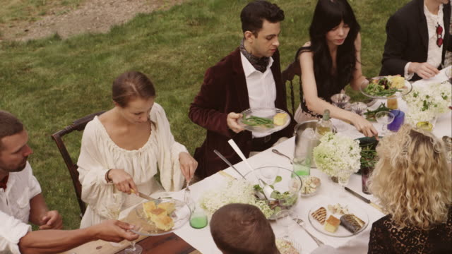friends and family eating at an outdoor dinner party - festlich gekleidet stock-videos und b-roll-filmmaterial